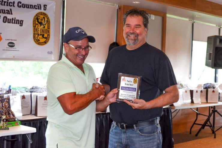 Don Long, representative for Thomarios, accepts appreciation plaque for their Beverage sponsorship.